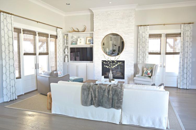 neutral living room qautrefoil drapes kravet Thurston wing chair round gold mirror seagrass rug