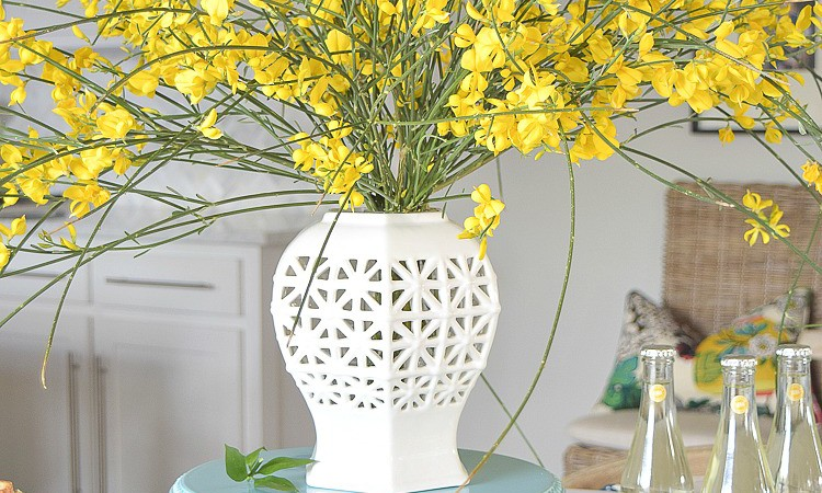 white vase spring brunch forsythia stems