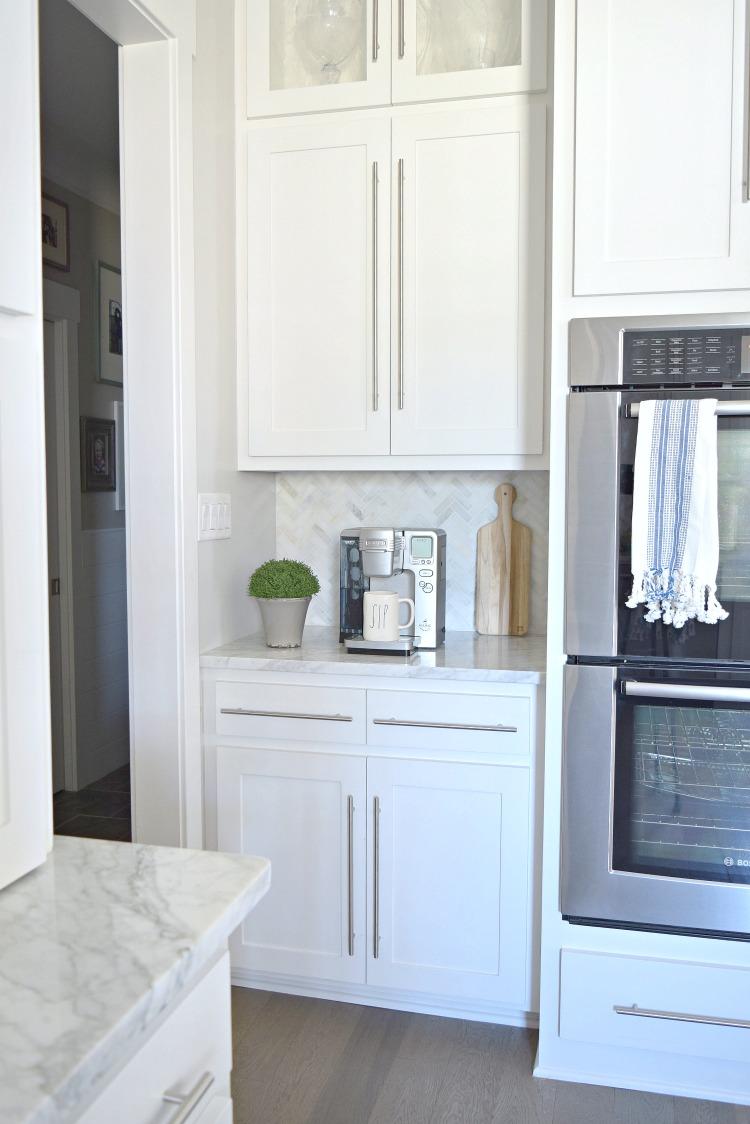 modern white kitchen coffee bar herringbone backsplash Carrara marble countertops
