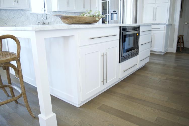 white kitchen island carrara marble counter tops herringbone backsplash modern shaker cabinets