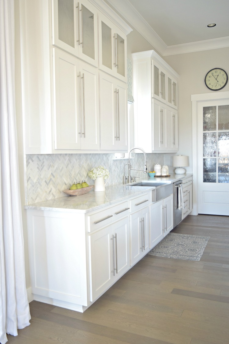 white kitchen stainless farmhouse sink herringbone backsplash carriara marble counter tops