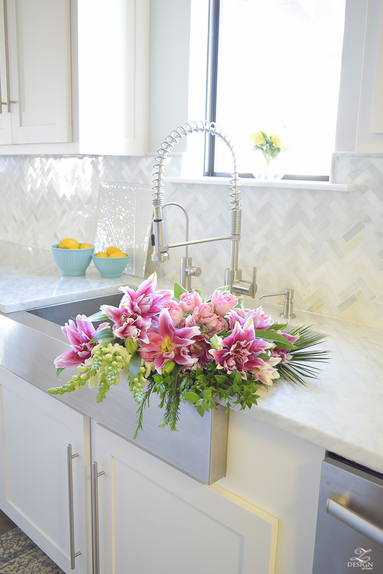 pink lillies white snap dragons flowers in the sink white kitchen
