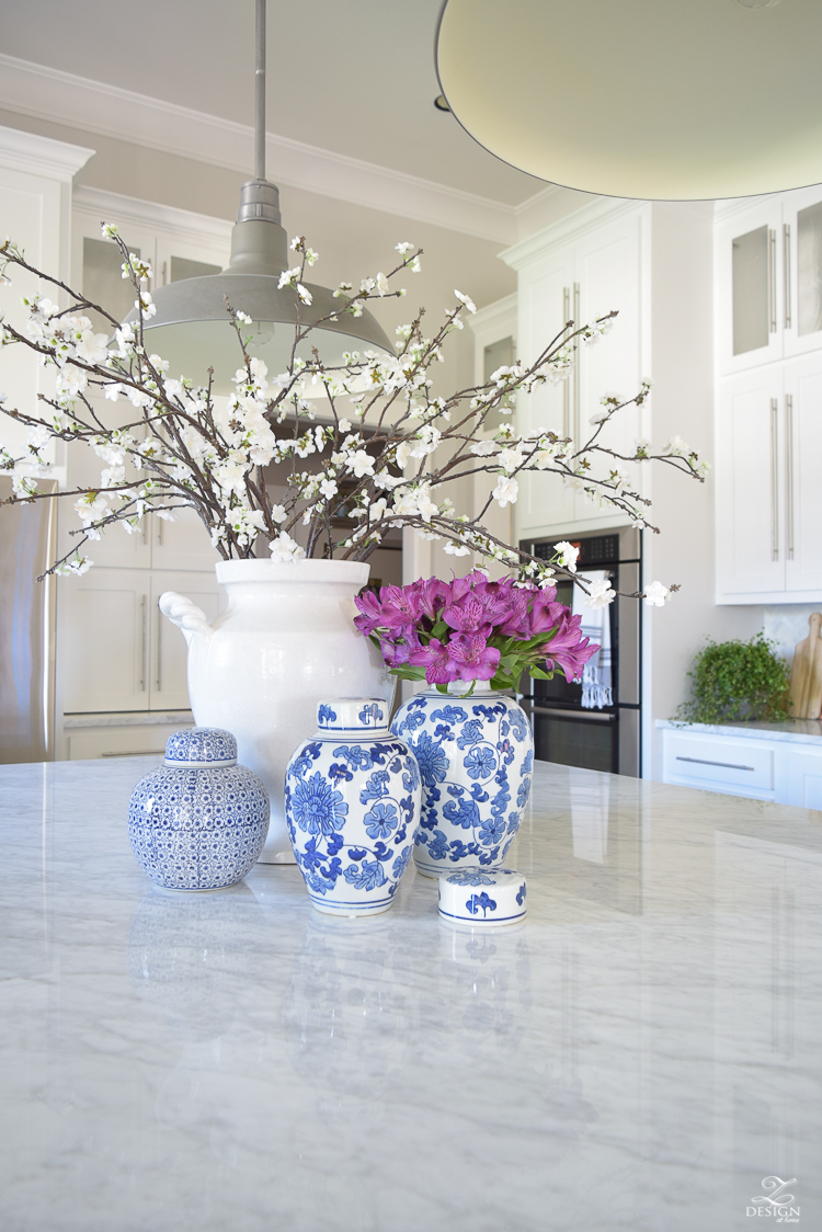 kitchen-island-styling-ideas-with-collection-of-vases-white-carrara-marble-farmhouse-pendants-chinoserie-blue-and-white-vases-4
