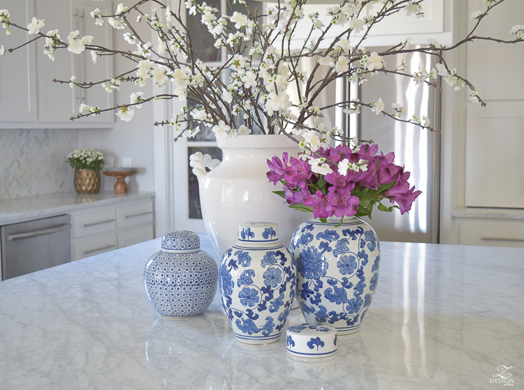 kitchen-island-styling-ideas-with-collection-of-vases-white-carrara-marble-farmhouse-pendants-chinoserie-blue-and-white-vases-6