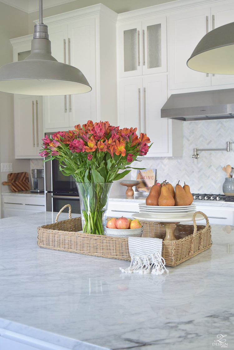 kitchen-island-styling-tips-with-baskets-fruit-and-flowers-carrara-marble-white-kitchen-herrinbone-backsplash-tile-1