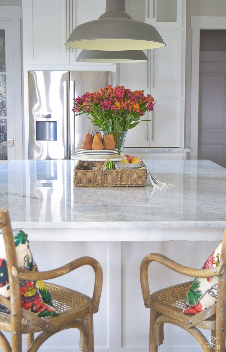 kitchen-island-styling-tips-with-baskets-fruit-and-flowers-carrara-marble-white-kitchen-herrinbone-backsplash-tile-3