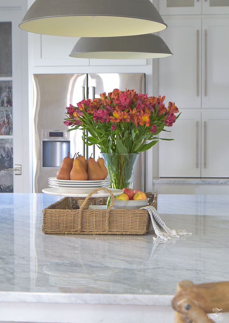kitchen-island-styling-tips-with-baskets-fruit-and-flowers-carrara-marble-white-kitchen-herrinbone-backsplash-tile-4
