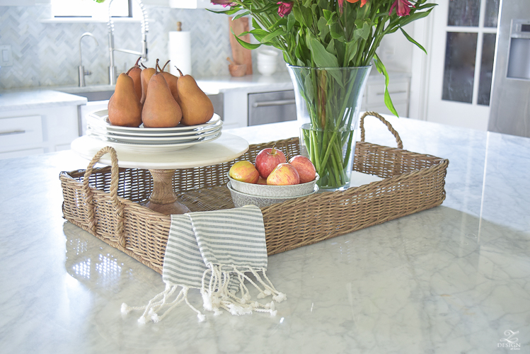 kitchen-island-styling-tips-with-baskets-fruit-and-flowers-carrara-marble-white-kitchen-herrinbone-backsplash-tile-5