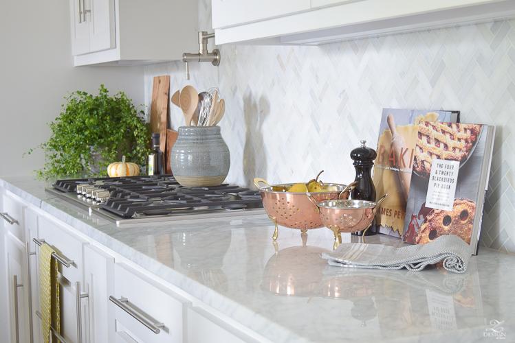 modern-fall-decor-in-the-kitchen-white-carrara-countertops-white-carrara-herringbone-backsplash-brass-pot-2