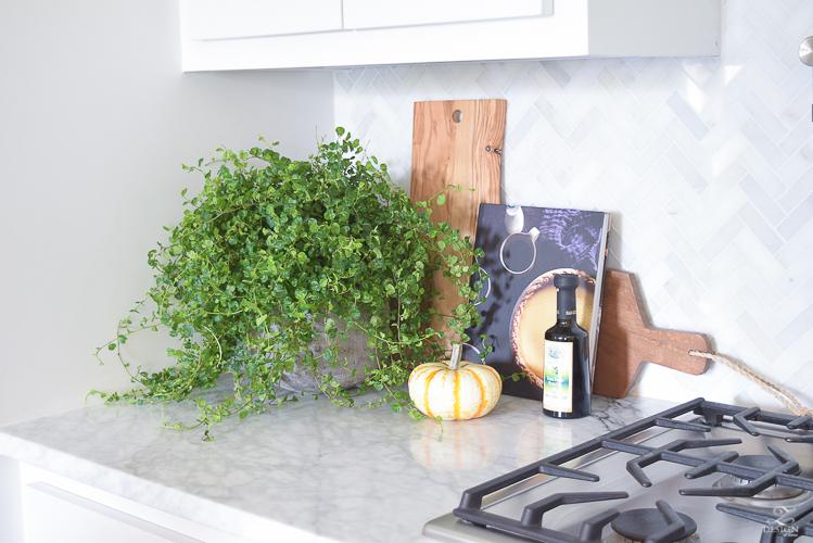 modern-fall-decor-in-the-kitchen-white-carrara-countertops-white-carrara-herringbone-backsplash-brass-pot-white-pumkins-1