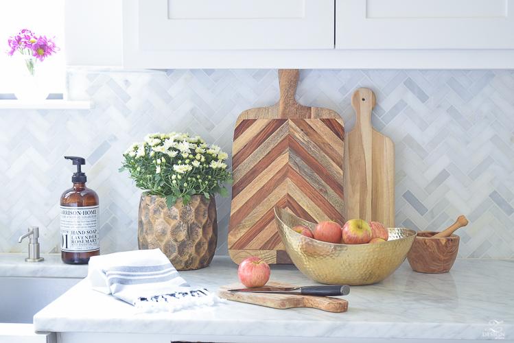modern-fall-decor-in-the-kitchen-white-carrara-countertops-white-carrara-herringbone-backsplash-brass-pot-white-pumkins-3