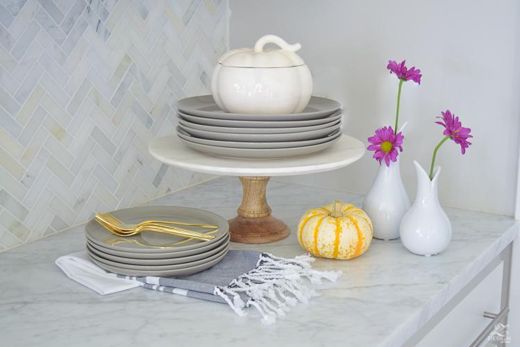 modern-fall-decor-in-the-kitchen-white-carrara-countertops-white-carrara-herringbone-backsplash-brass-pot-white-pumkins-6