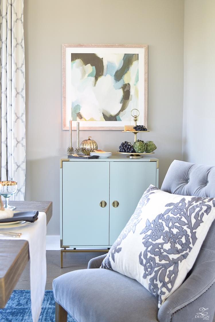 teal-bar-cabinet-minted-abstract-art-golden-bamboo-lamp-vining-velvet-pillow-3