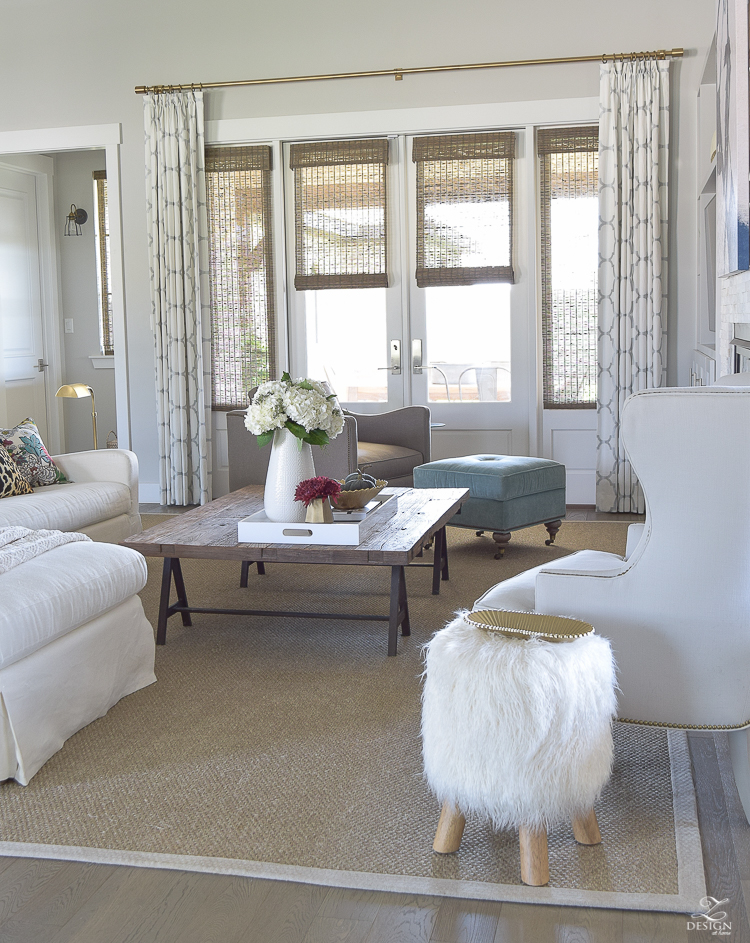 transitoinal-living-room-tour-restoration-hardware-couch-chaing-mia-dragon-fabric-seagrass-rug-navy-abstract-art-white-hydrangeas-fur-stools-7