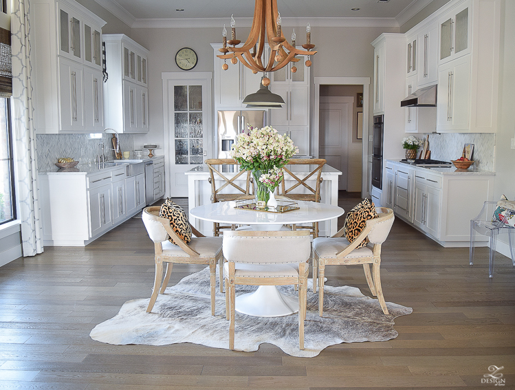 get-the-curl-out-of-cowhide-rug-white-farmhouse-kitchen-white-tulip-table-white-carrara-marble-marble-herringbone-tile-backsplash-4