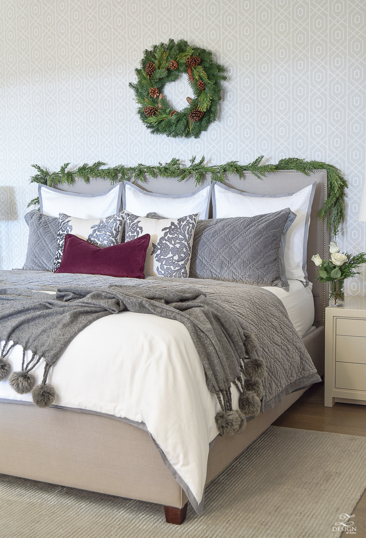 christmas-tour-bedroom-white-bedding-geometric-wallpaper-wreath-and-garland-on-headbaord-pom-pom-throw-upholstered-nailhead-bed-2