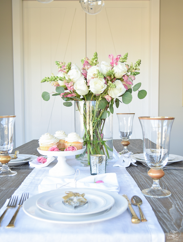 Valentines tablescape crystal heart ornament white fur throw flower arrangement with white roses pink snap dragons white cupcakes white dishes-7