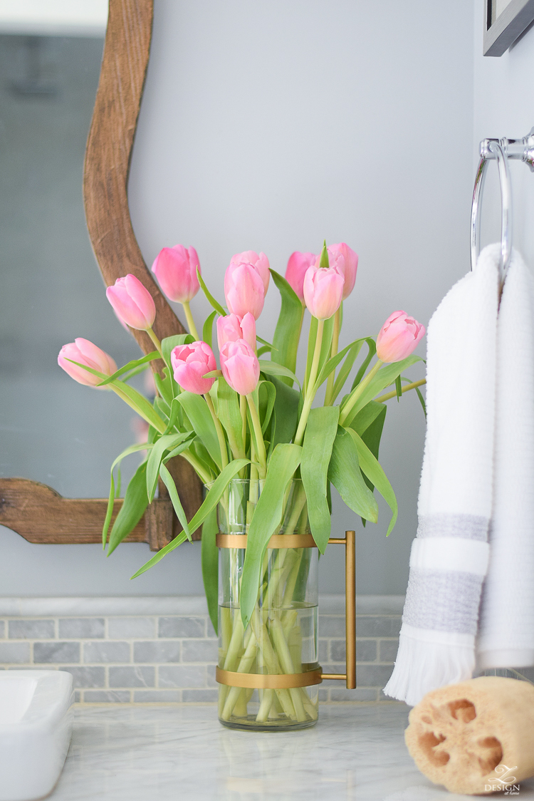 spring bathroom refresh brass and marble accessories wooden mirror white carrara marble brass and glass pitcher pink tulips marble backsplash-1