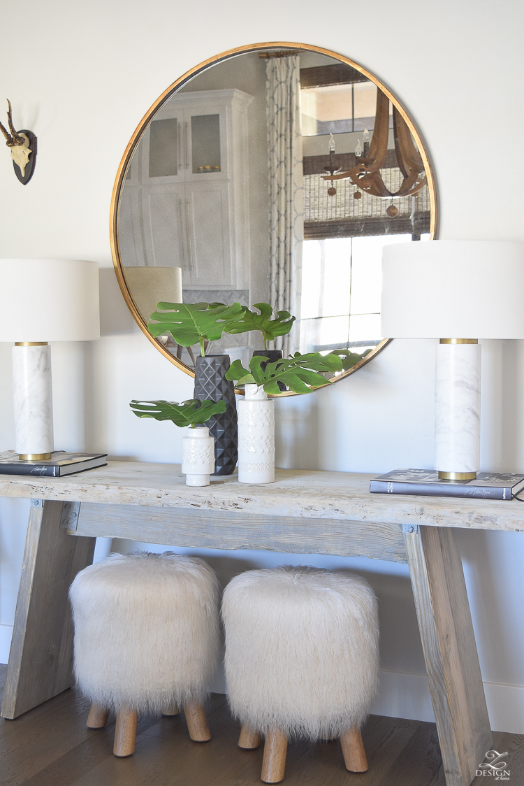 zdesign at home spring tour rustic console with round gold mirror fur stools philadendron branches white global inspired vases gray wood floors marble and brass lamps-1