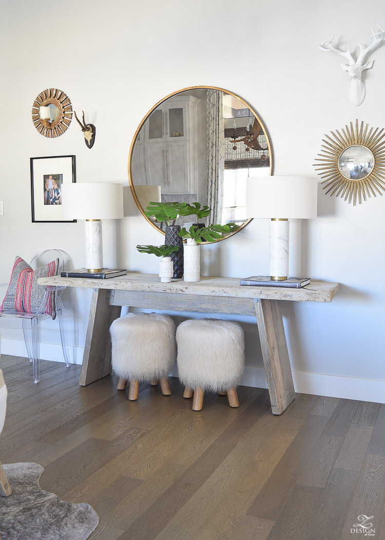 zdesign at home spring tour rustic console with round gold mirror fur stools philadendron branches white global inspired vases gray wood floors marble and brass lamps-2