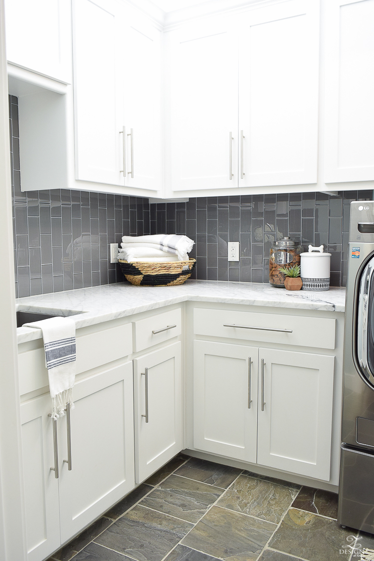 Beautiful Laundry Room Ideas White shaker cabinets large stainless bar pulls carrara marble counter tops gray glass subway tile laid vertiacally marble in the laundry room slate tile floors-2