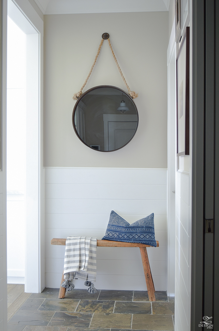 Hall way design rustic bench with tassel throw and hmong pillow round black mirror slate flooring white tounge and groove walls-2