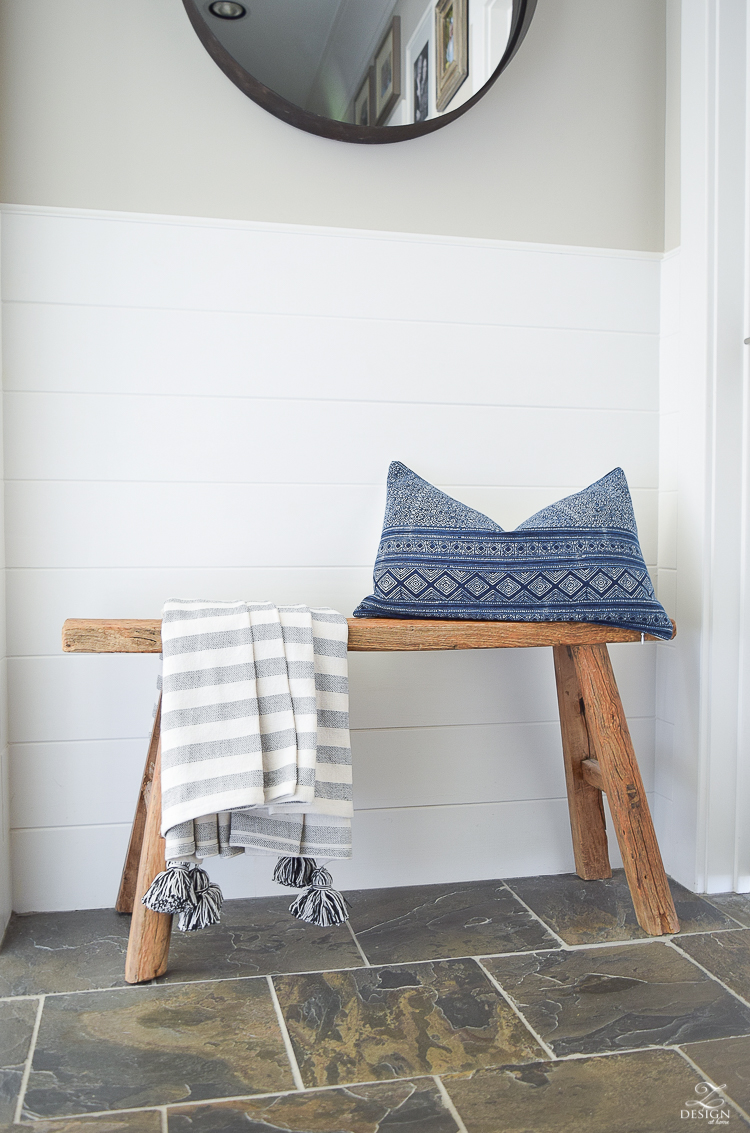 Hall way design rustic bench with tassel throw and hmong pillow round black mirror slate flooring white tounge and groove walls-3