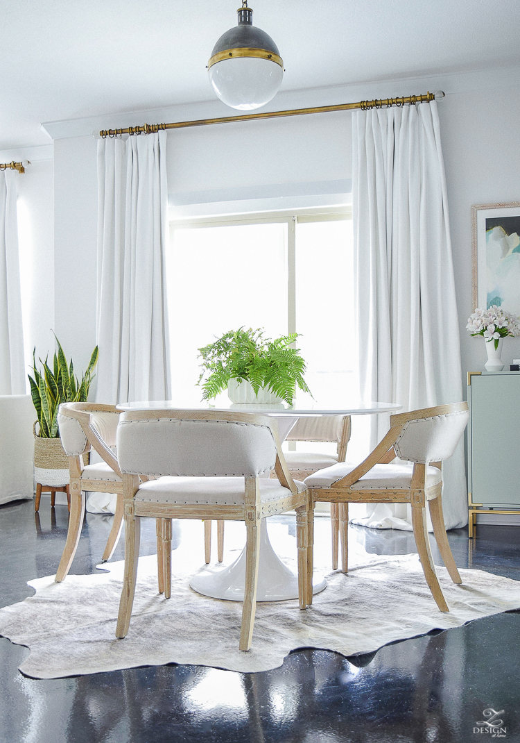 tulip table on cow hide rug white linen drapes with brass rod black concrete floors hicks pendant mid mod dining space geometric modern white flower pot-2