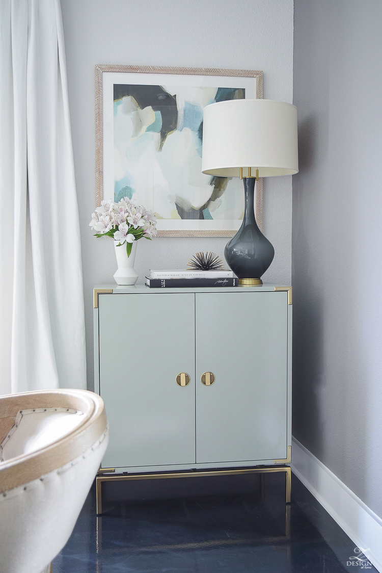 white linen drapes brass rod with crystal ball minted art gray lamp with brass base teal bar cabinet with brass accents black concrete floors console table styling-6