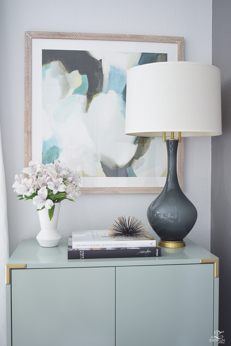 white linen drapes brass rod with crystal ball minted art gray lamp with brass base teal bar cabinet with brass accents black concrete floors console table styling-7