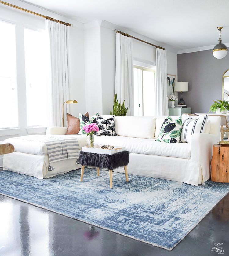 zdesign at home summer home tour blue vintage inspired rug white slip covered couch white walls white linen drapes black fur stool black and white pillows leather pillow-6
