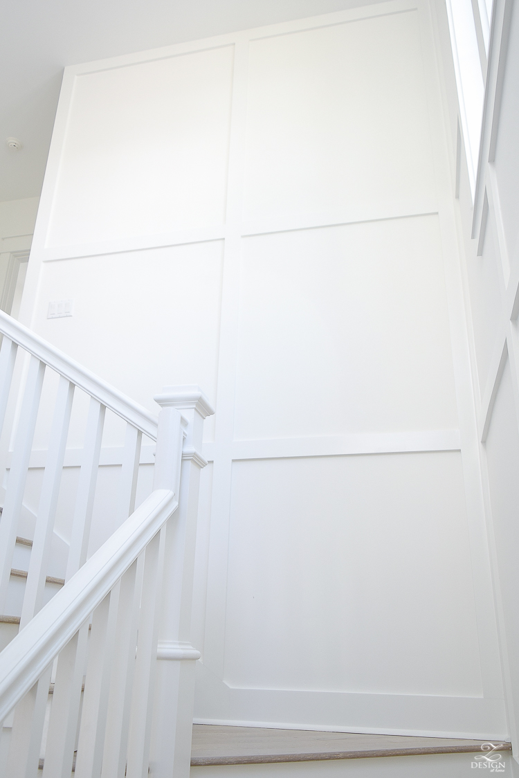grid wall pattern in staircase with white walls blonde distressed hardwood floors chrome coastal chandelier beach house design coastal house decor how to design a beach house-4