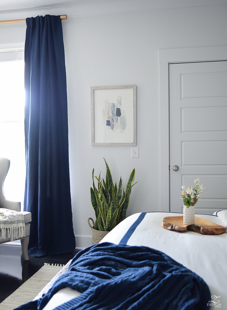 Minted abstract art Bedroom reveal navy linen curtains with blackout liner snake plant in basket navy and white banded bedding transitional style master bedroom-1