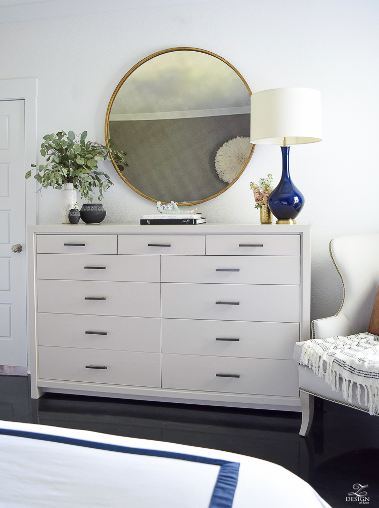 Transitional style master bedroom round gold mirror navy lamp with brass base dresser styling bedroom dresser decor modern gray dresser-3