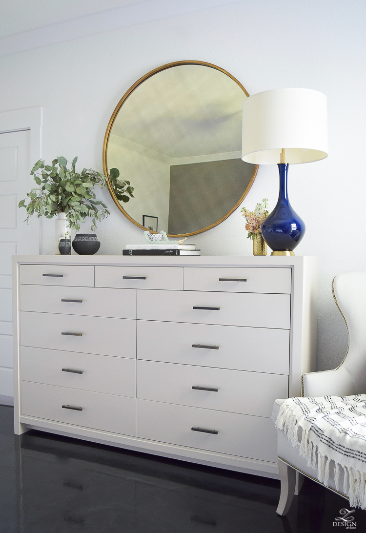Transitional style master bedroom round gold mirror navy lamp with brass base dresser styling bedroom dresser decor modern gray dresser-4