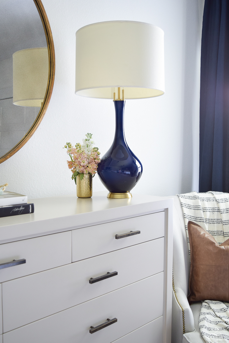 transitional style bedroom decor navy lamp with brass base round gold mirror modern gray dresser gold pencil cup-1