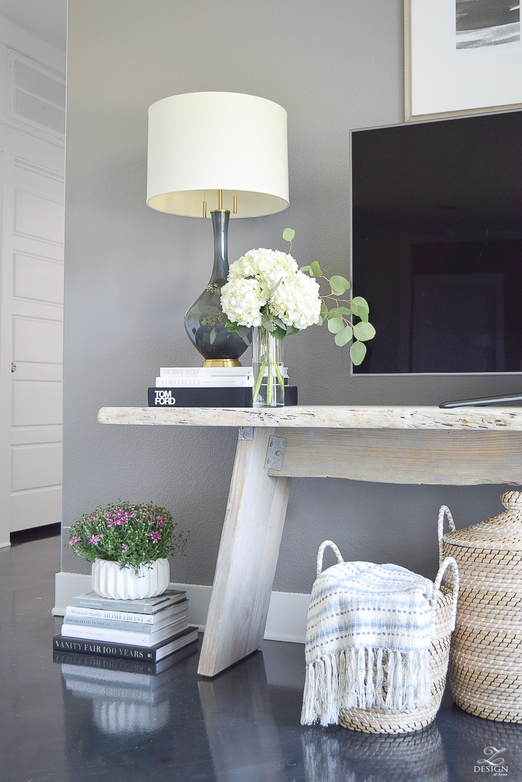 Fall Home Tour Decorating with books gray and brass table lamp distressed modern console table black concrete floors books stacked on floor with plant on top white fluted pot-1