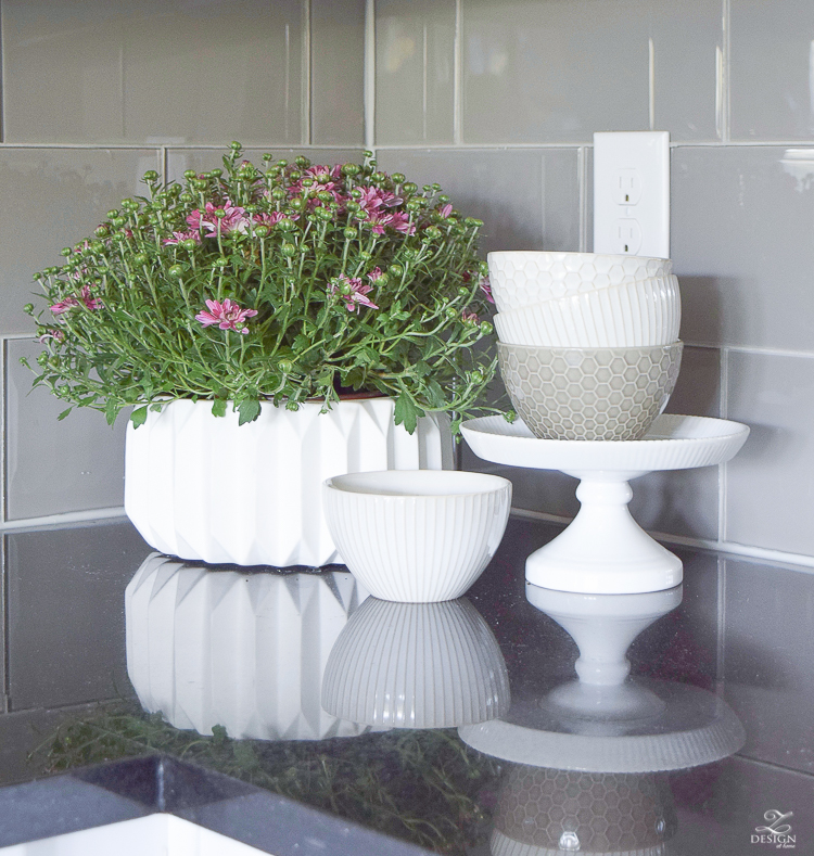 plum mums in a fluted pot white and gray geometric dishes
