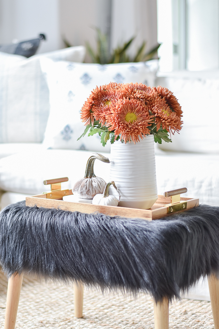 Simple, Modern Fall Decorating Ideas - black fur stool, orange mums, velvet pumpkins