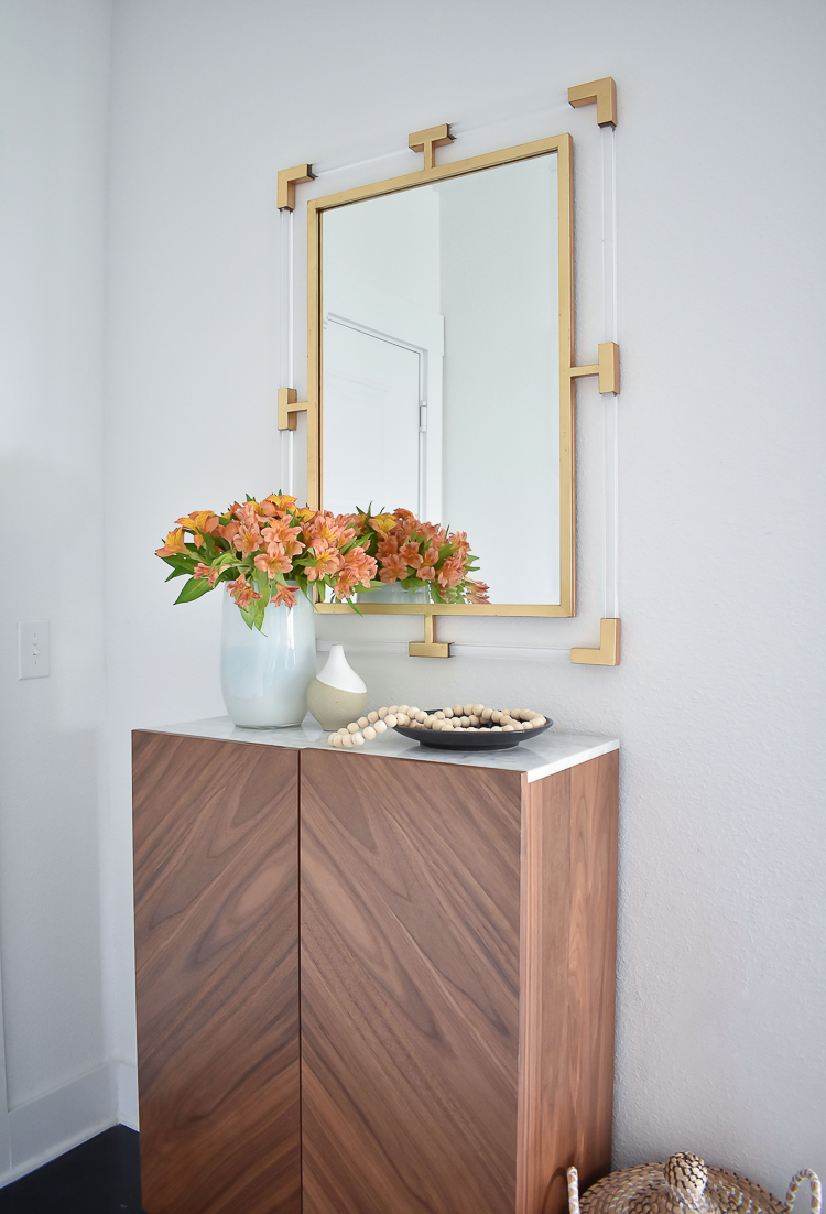 Small Transitional Entry That Packs A Big Punch - marble top shallow entry way cabinet and lucite gold mirror