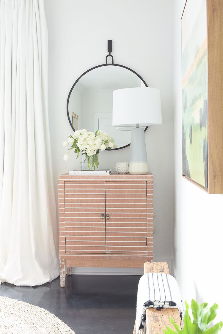 Zdesign At Home Spring Dining Room Tour - modern wooden bar cabinet with accessories - black round mirror