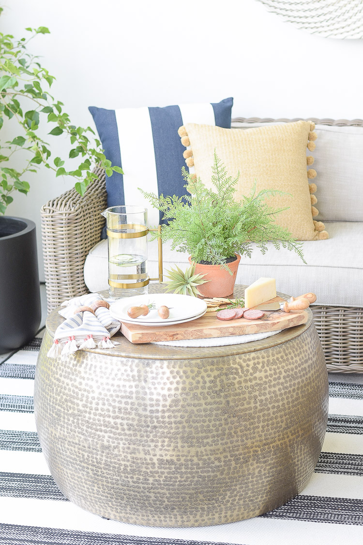 Sustainably sourced outdoor home decor - pillows, cheese board, round gold hammered coffee table, water pitcher