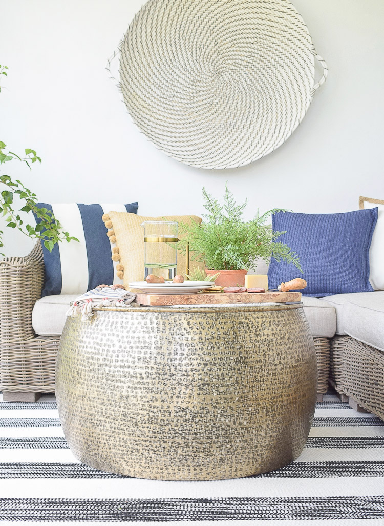Sustainably source outdoor furniture and accessories - pom pom pillows, cheese board, hammered gold coffee table