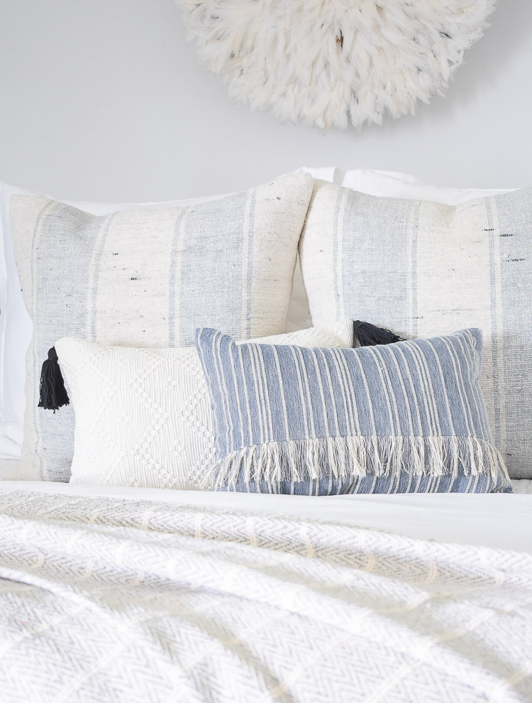 4 Subtle Ways To Add Coastal Decor To Your Home - Coastal Inspired Bedroom - white pillow with black tassels