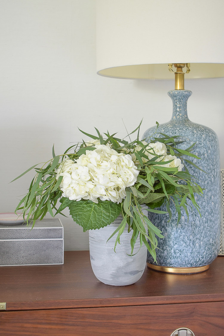 white hydrangeas, eucalyptus in cement vase