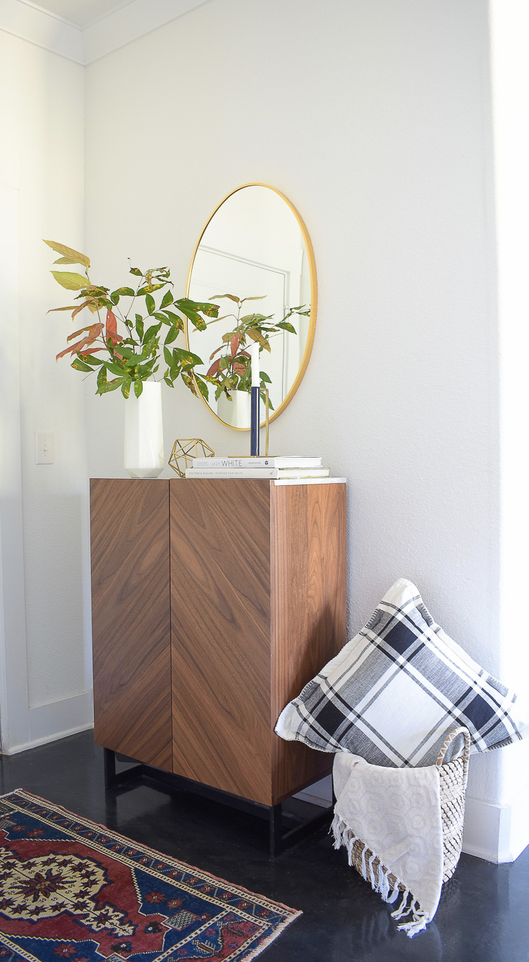 Chic modern fall styled entry - oval gold mirror, geometric gold home accessories