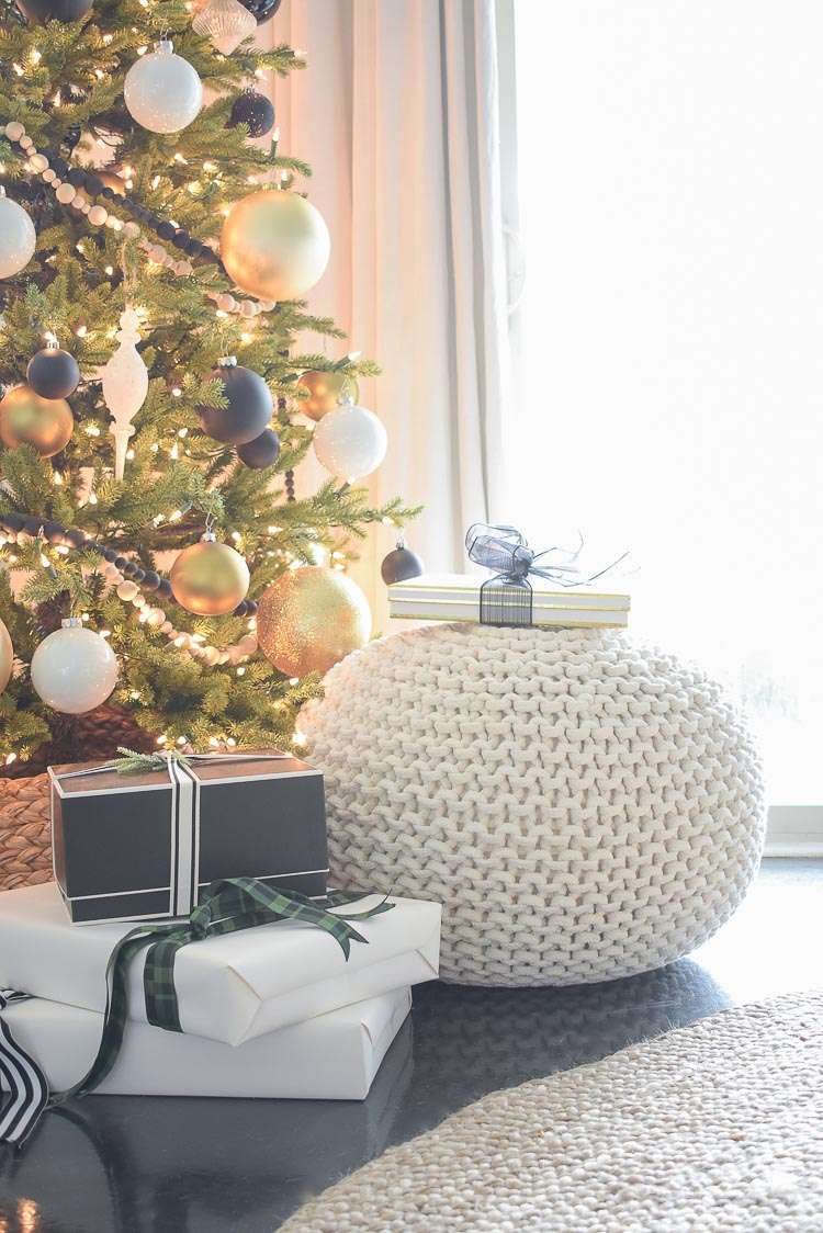Black and white modern gift wrap / white knit pouf styled under tree for Christmas