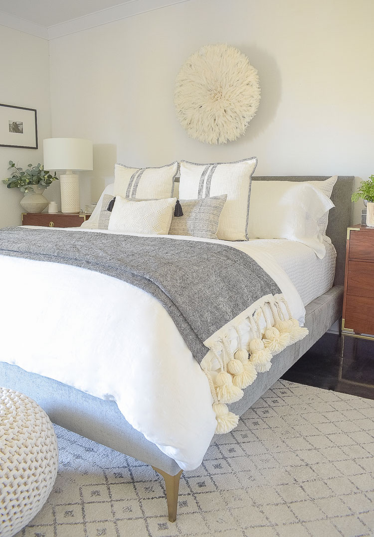 black and white spring bedroom tour - large tassel throw over end of bed