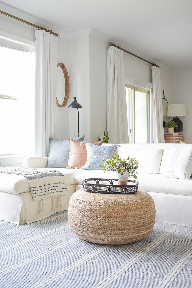 Spring Living Room Tour - round jute ottoman in boho chic living room with white sofa and curtains