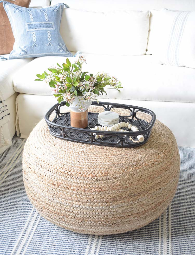 Spring flower arrangement on coffee table / jute round ottoman